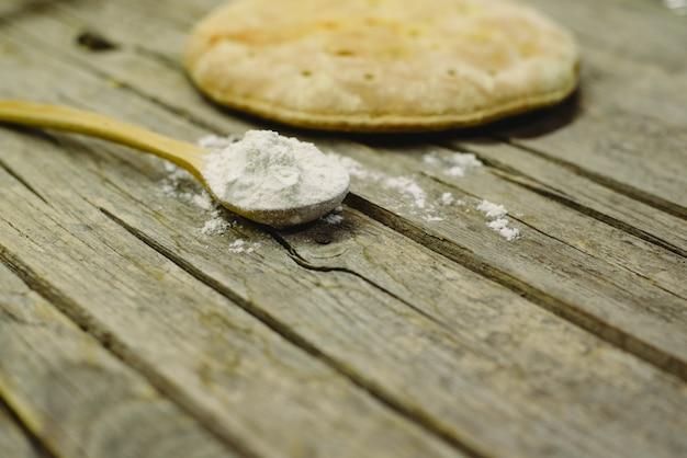 Calzone di pizza appena sfornato su tavola di legno invecchiato con cucchiaio pieno di farina