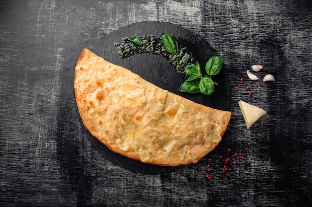 Calzone tradizionale pizza italiana con ingredienti su una pietra e fondo in legno scuro graffiato