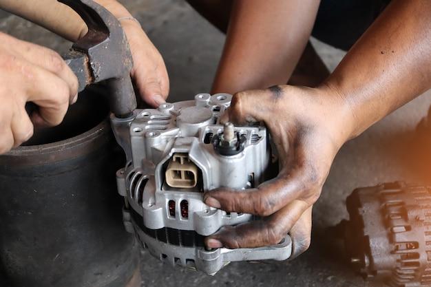 Cambia il nuovo alternatore per auto con la mano nel garage o nel centro di assistenza per la riparazione automatica, come tonalità scura automobilistica.