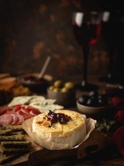 Camembert al forno con marmellata, salsiccia, gorgonzola, olive e snack, su una tavola di legno, bicchieri con vino rosso
