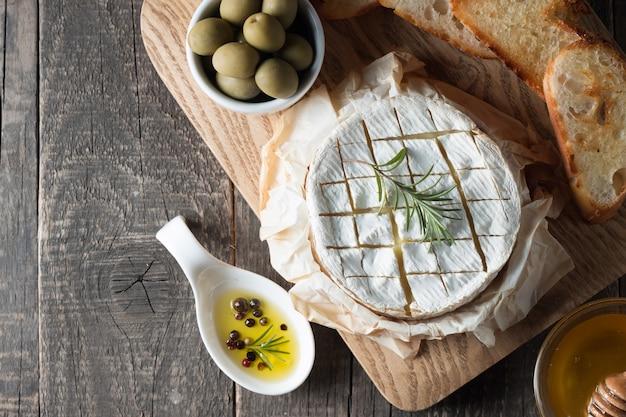Camembert e brie su legno con pomodori, lattuga e aglio. cibo italiano. latticini.