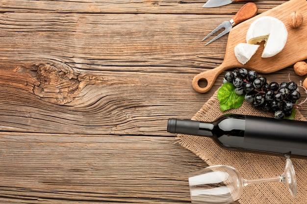 Camembert piano di disposizione sull'uva e sulle noci del tagliere di legno con lo spazio della copia