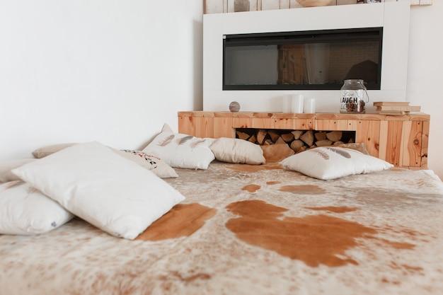 Camera da letto casa di campagna con pelle di mucca naturale sul letto in legno e camino