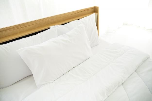 Camera da letto decorata in stile minimalista, fotografia di cuscini bianchi e letto in legno in camera da letto con luce naturale dalla finestra.
