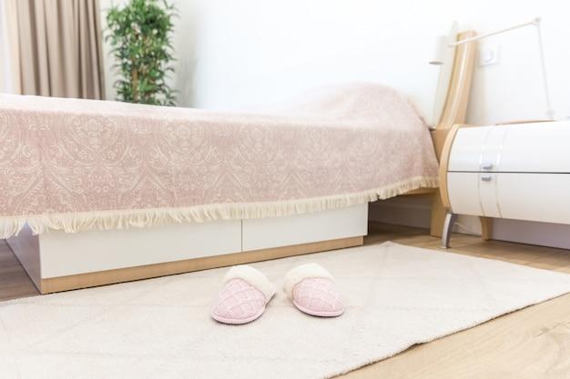 Camera da letto in stile moderno con morbide e morbide pantofole rosa sul pavimento
