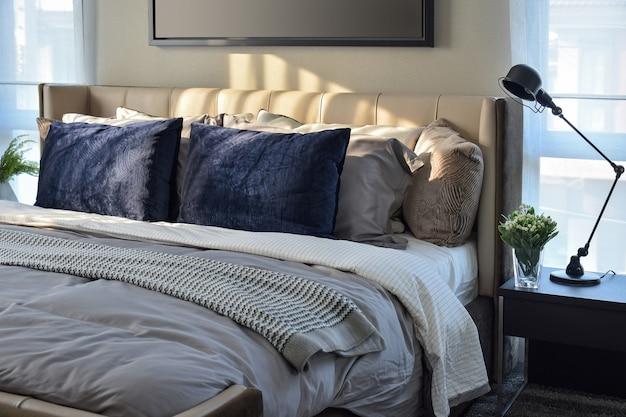 Camera da letto moderna con cuscini blu e lampada nera sul tavolo