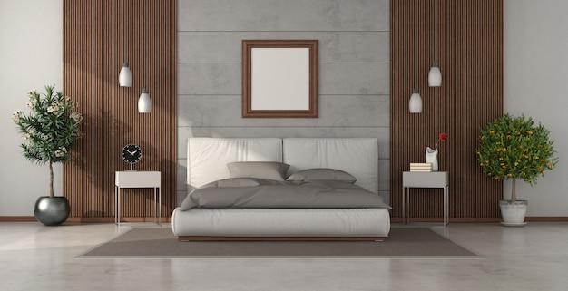Camera da letto moderna con letto matrimoniale contro il muro di cemento