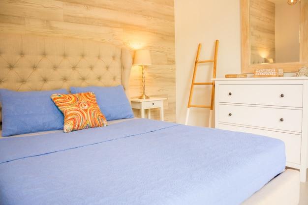 Camera da letto moderna, cuscini fantasia, lampada, finestre