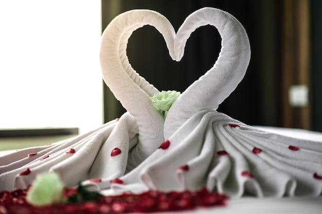 Camera da letto sposi, camera da letto di lusso, biancheria bianca, cigno bianco, petalo rosso, cuore rosso