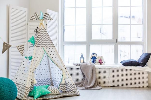 Camera per bambini moderna ed elegante. wigwam per bambini nella stanza dei bambini. grande lampada a stella in legno. interni in stile scandinavo.