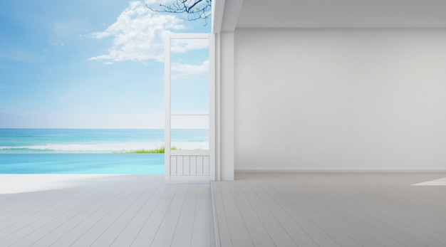 Camera vista mare della lussuosa casa sulla spiaggia estiva con porta a vetri e terrazza sul pavimento in legno vicino alla piscina.