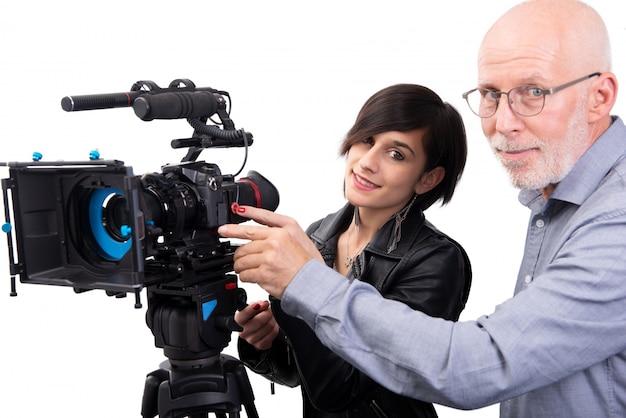 Cameraman e una giovane donna con una macchina da presa dslr su bianco