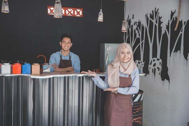 Cameriera che dà il benvenuto al cliente