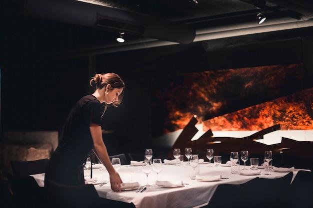 Cameriera che fissa il tavolo del banchetto