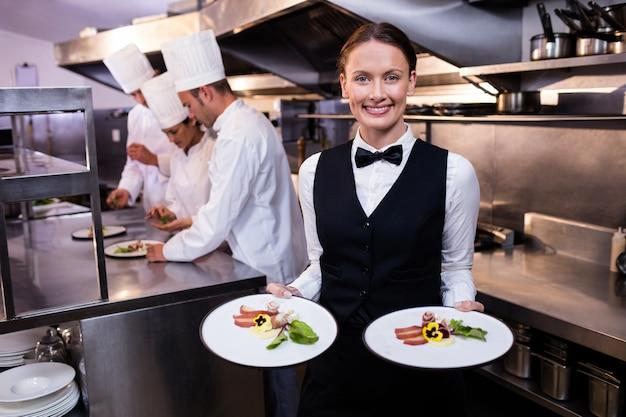 Cameriera che mostra i piatti alla macchina fotografica