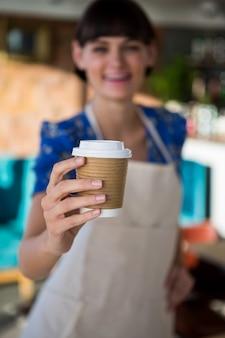 Cameriera che offre una tazza di caffè