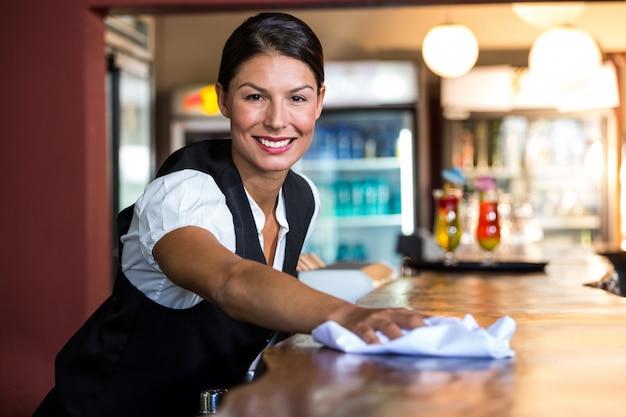 Cameriera che pulisce il bancone
