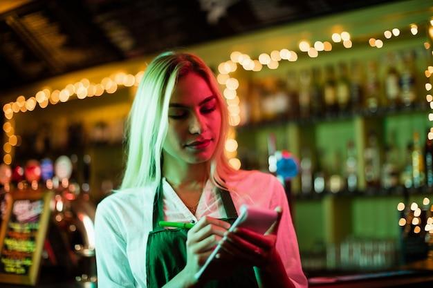 Cameriera che scrive un ordine sul blocco note
