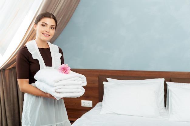 Cameriera con asciugamani puliti freschi durante le pulizie in una camera d'albergo