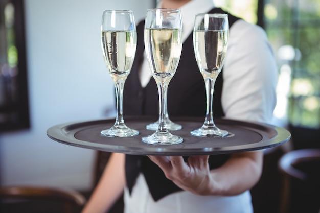 Cameriera con un vassoio di flauto di champagne