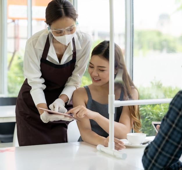 Cameriera con visiera e maschera che mostra il menu