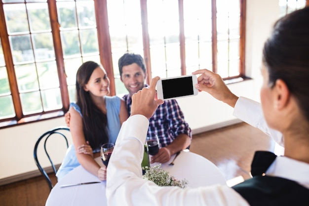 Cameriera di bar che fa clic sulla foto di una coppia in ristorante