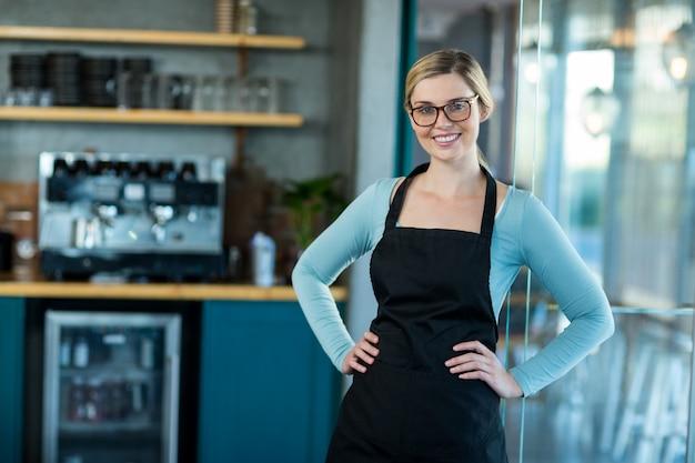 Cameriera di bar sorridente che mostra ardesia con il segno aperto