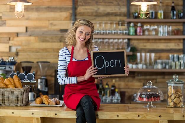 Cameriera di bar sorridente che si siede con l'insegna aperta in caffè