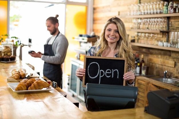 Cameriera di bar sorridente che sta al contatore e che mostra ardesia con il segno aperto