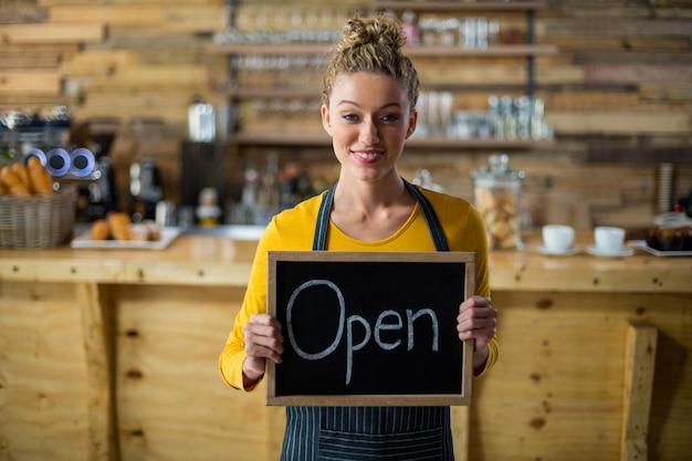 Cameriera di bar sorridente che sta con il bordo aperto del segno in caffè