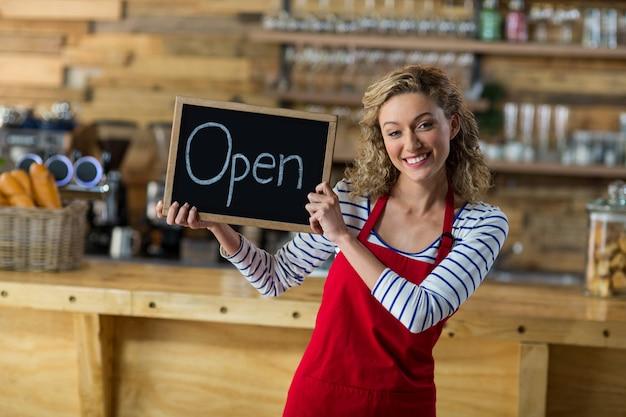 Cameriera di bar sorridente che sta con l'insegna aperta in caffè