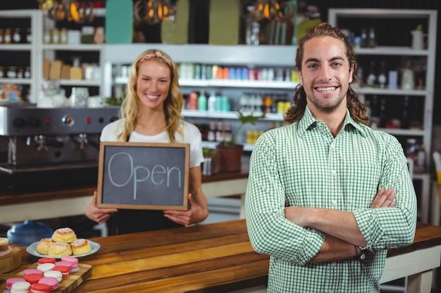 Cameriera di bar sorridente che sta con la lavagna della tenuta del cliente con il segno aperto