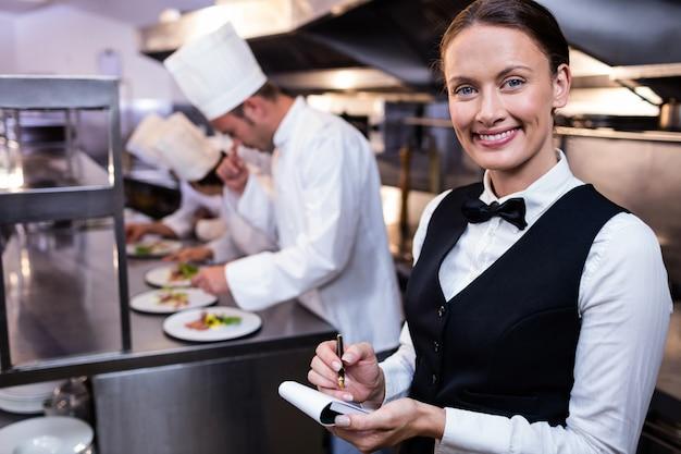 Cameriera di bar sorridente con il blocco note in cucina commerciale