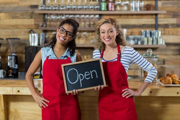 Cameriera di bar sorridente due che sta con l'insegna aperta in caffè