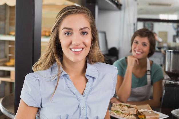Cameriera e cliente graziosi che sorridono alla macchina fotografica