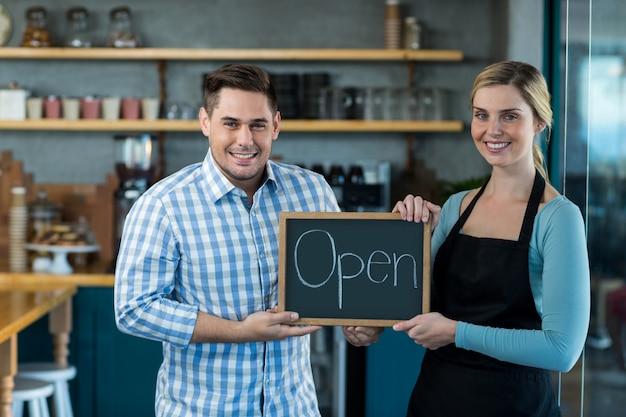 Cameriera e uomo che stanno con il segno aperto sull'ardesia in caffè