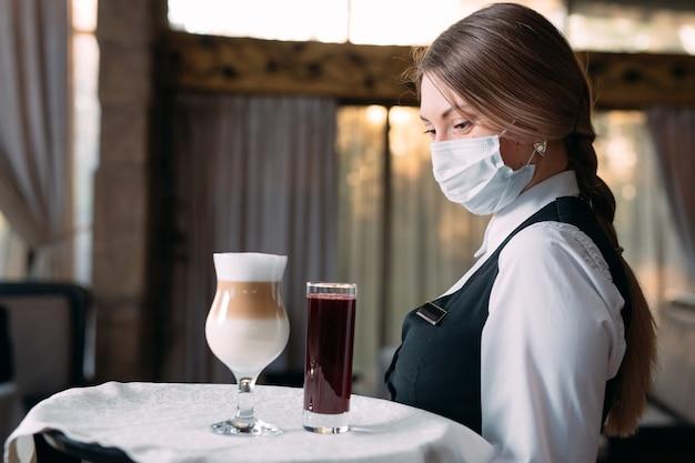 Cameriera femminile di aspetto europeo in una maschera medica serve caffè latte.