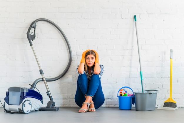 Cameriera femminile preoccupata che si siede vicino alle attrezzature di pulizia davanti al muro di mattoni