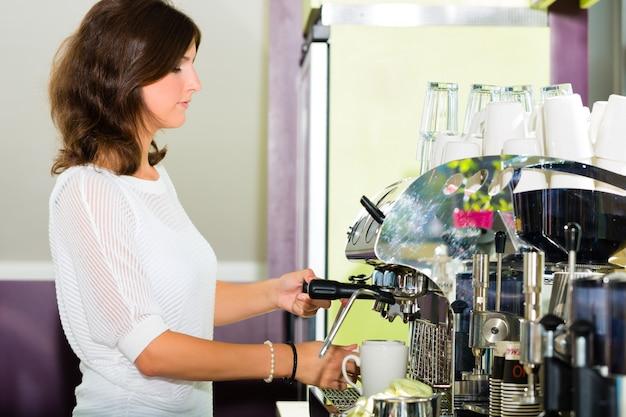 Cameriera in caffè a fare il caffè