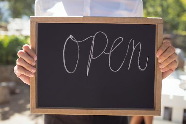 Cameriera in piedi con cartello aperto