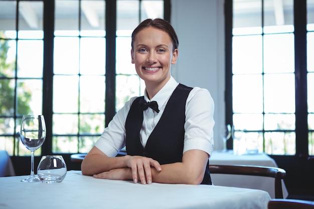 Cameriera in posa e seduto al tavolo