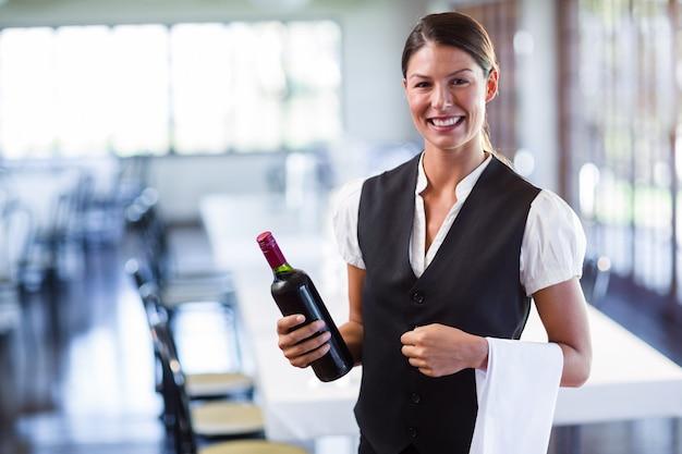 Cameriera in possesso di una bottiglia di vino rosso e un tovagliolo