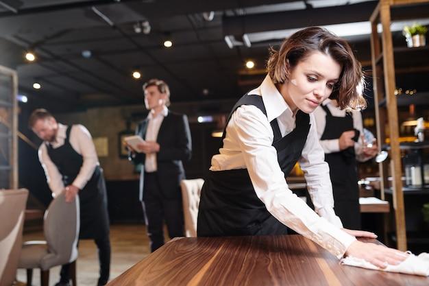 Cameriera occupata che prepara il ristorante per l'apertura e la pulizia