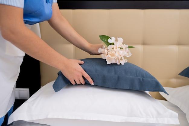 Cameriera professionista chinandosi sul letto mentre mette fiori freschi sopra il cuscino mentre prepara la stanza per gli ospiti