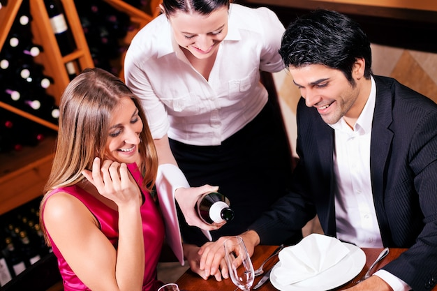 Cameriera riempimento bicchieri di champagne