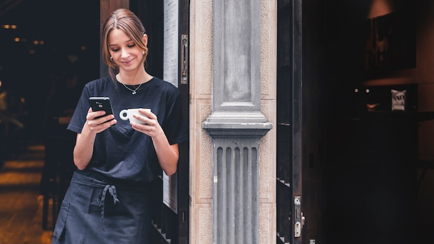 Cameriera sorridente con bevanda usando smartphone