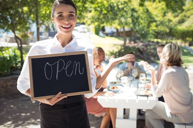 Cameriera sorridente in piedi con cartello aperto