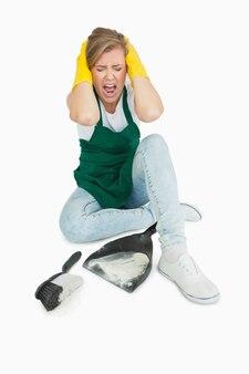 Cameriera stanca che urla mentre si siede con la spazzola e la vaschetta per la polvere