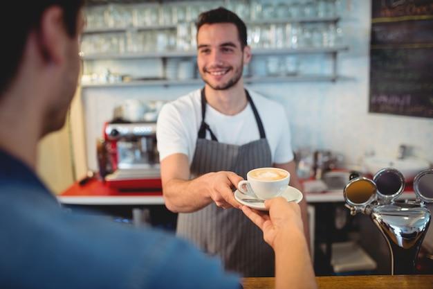 Cameriere bello che serve caffè al cliente maschio al self-service