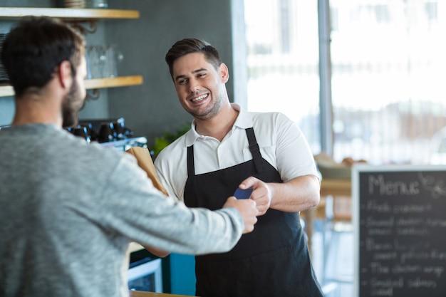 Cameriere che dà il pane al cliente al bancone